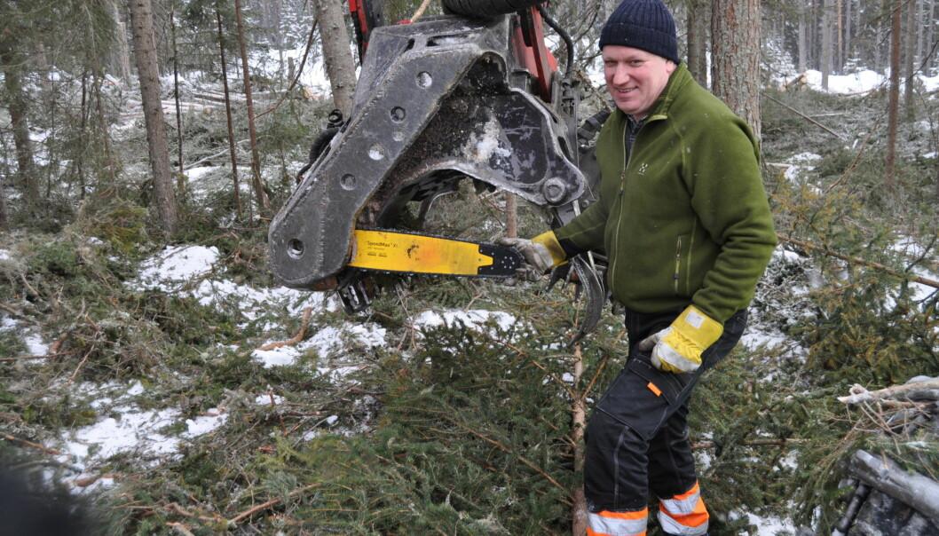 Snödjupet döljer mer än trädstammar. Åke Eliasson byter sågkedja på skördaren.