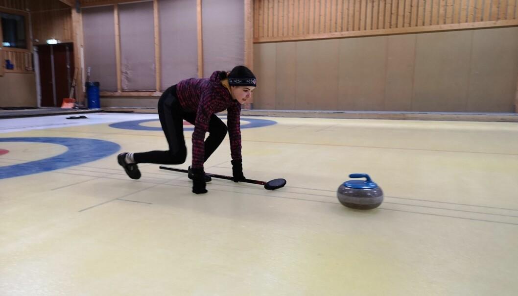 Nomi slidar över curlingbanan redo att sopa in stenen i boet på andra sidan.