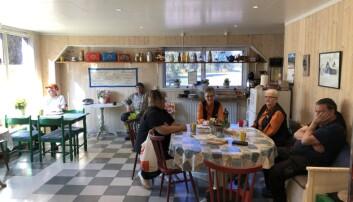 Eivor i orange skjorta och Doris till vänster om henne, också i orange skjorta, med några av sina kunder i butikens fik. Längst till vänster sitter Helge Andersson som kommer in klockan sju varje morgon och dricker kaffe.