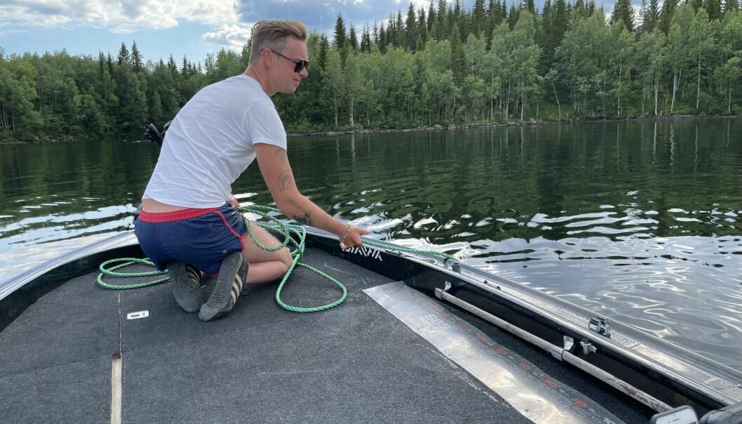 Oscar Herlitz, sportfiskare, är orolig över bland annat farorna med lösa tampar som slitit sig från Vattudalens Fisk AB. De kan orsaka tvärnitar och motorhaveri. Här fiskar han upp en lina som han bedömer vara cirka tio meter lång. Tack vare sol och vindstilla upptäckte Oscar tampen i tid.