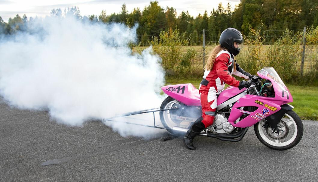 Linnea varvar upp sin motorcykel lägger i ettan och släpper sakta kopplingen och slirar igång. Handbromsen låser framhjulet.