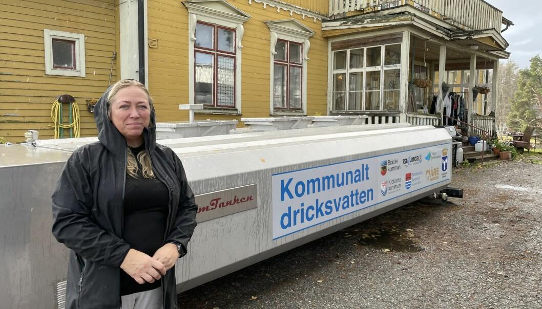 Marie Åhlstedts dricksvatten började lukta och smaka fränt i slutet på augusti. Lukten påminner om kylarvätska. Vattenproverna påvisade bland annat halter av bensen. Bakom Marie står vattentanken som kommunen körde till hennes tomt förra veckan.